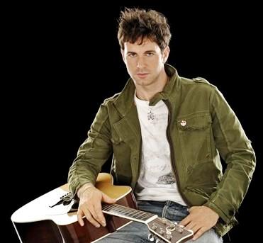 Foto de Axel sentado con su guitarra