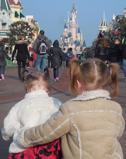 Toddlers sitting in front of Disneyland Paris Castle