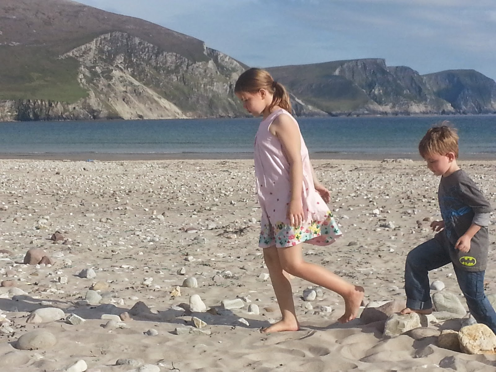 a young girl and young boy walking on keel beach with th minaun cliffs in the backgound