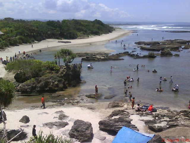 wisatawan berenang mengunakan ban di pantai santolo