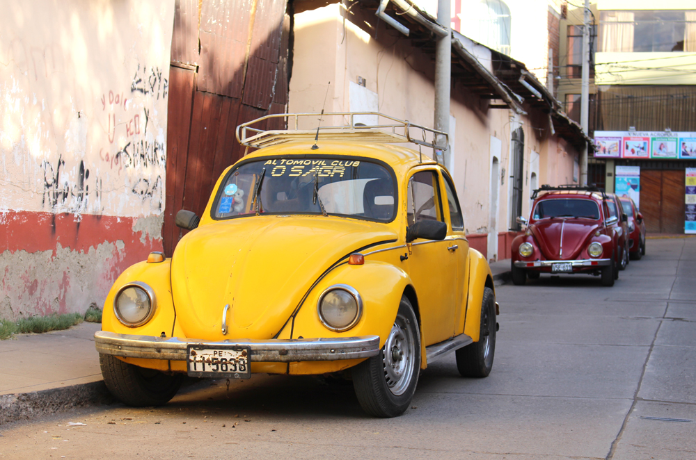 Old yellow car in Puno, Peru - travel blog