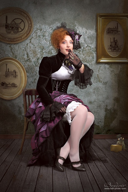Woman wearing steampunk clothing in shades of purple. Velvet bolero jacket, corset, purple skirt, hat, ruffle jabot, blouse.