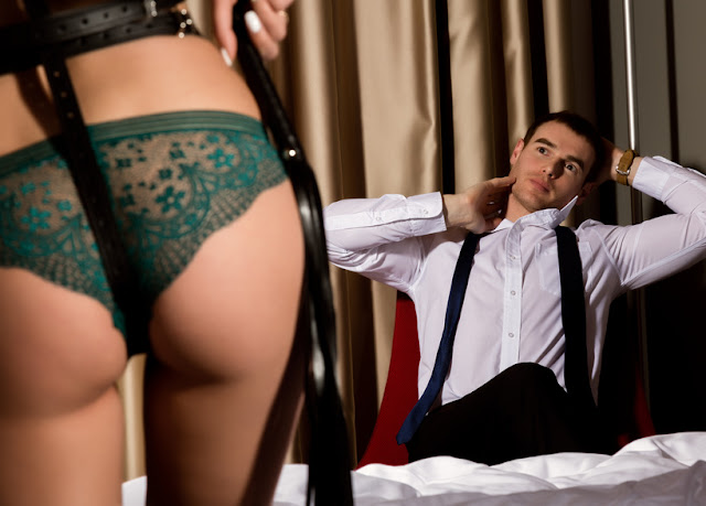 sexy womans buttocks in underwears with a whip standing in front of handsome guy. BDSM concept