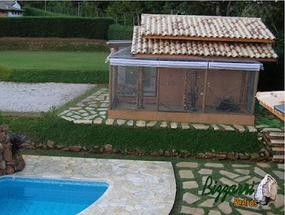 Construção da piscina com cascata de pedra com o viveiro dos pássaros, os muros de pedra com os caminhos de pedra e o piso da piscina com pedra São Tomé.