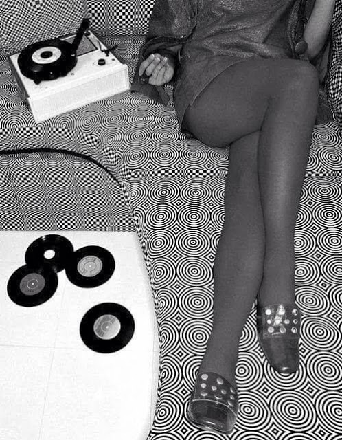 Mod photo of a woman's body in a mini dress, sitting on sofa in graphic print, listening to singles on a small record player. Pirate Radio and Sealand and Other stories of Rock, Radio, and Regulations. Marchmatron.com