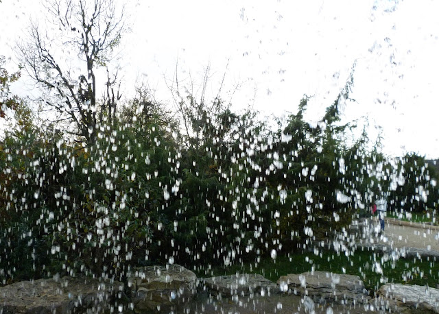 A photograph looking out through an ornamental waterfall so that it looks like heavy rain