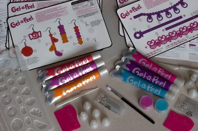 The contents of two Gel-a-Peel kits used to decorate the cards. There are patterns, a mould, 6 tubes of gel, earring , fuzz, nozzles, scrapers and a brush