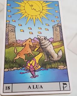 Tarot Universal de Waite - Carta 18 – A Lua   Descrição: No topo, sobreposto a um céu azul claro, a Lua cheia dourada bem brilhante, dentro, o perfil de um rosto permite perceber outra lua, a crescente; dezenove respingos caem da lua. Ao centro, sobre a relva, dois lobos observam a energia que emana da Lua; próximo aos lobos, um lagostim à beira d'água em posição de ataque. Nas laterais, uma torre de cada lado, entre os lobos, um caminho estreito que percorre a região em linha sinuosa em direção aos morros, ao fundo.   Significa que as emoções estão em alta podendo trazer ilusões, enganos e inseguranças. Aumento da capacidade psíquica e o que estava escondido pode aparecer: os mistérios e segredos. A falta de clareza causada pelo excesso de emoções e sentimentos pede momentos de reflexão.   Dia 17 acontece a primeira Lua Nova de 2018 às 00h12 em Capricórnio.