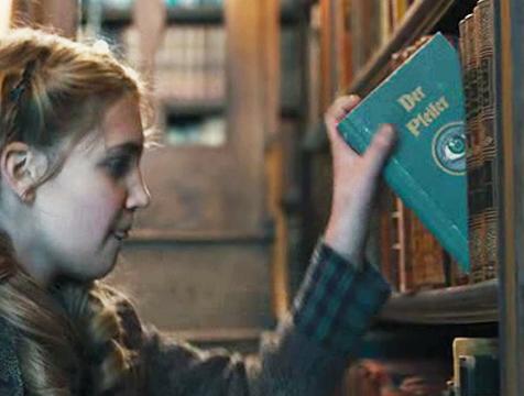 Liesel Meminger (Sophie Nélisse) cogiendo un libro de la casa del alcalde en La ladrona de libros - Cine de Escritor