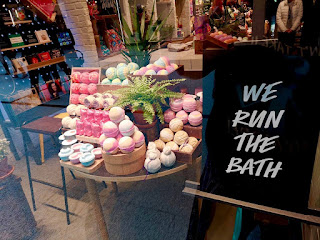 A tall rectangular portraitt black board with We Run The World in bright white casual font next to a large light brown table containing seven different coloured spherical bath bombs on a bright background