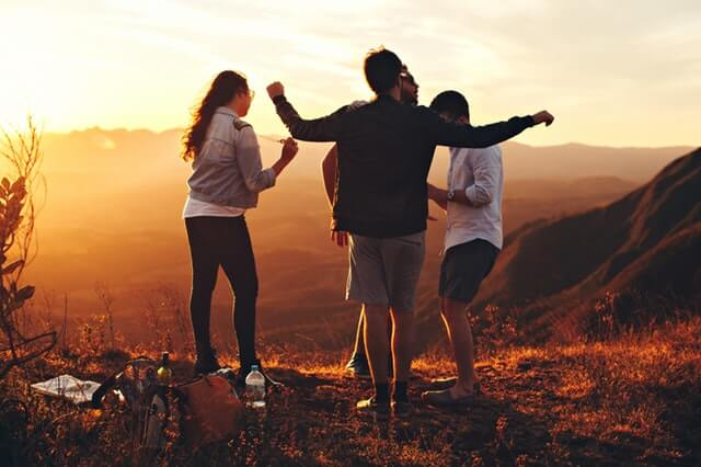 Four Person Standing at Top of Grassy Mountain HD Copyright Free Image