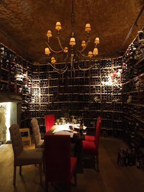 Mesa en medio de una bodega, con las paredes cubiertas de botellas de vino