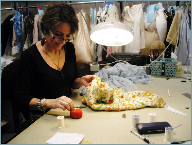 La costumière Samia, s'affairant à la réfection du perlage d'un costume