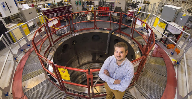 Sandia National Laboratories' Guillaume Loisel poses with Sandia's Z machine, where hands-on experiments contradicted a long-standing assumption about the X-ray spectra from the vicinity of black holes in space. Loisel is the lead author of a paper on the experimental results, published in Physical Review Letters. (Photo by Randy Montoya)
