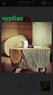 В комнате стоит стол на колесах, который сделан из чурбака