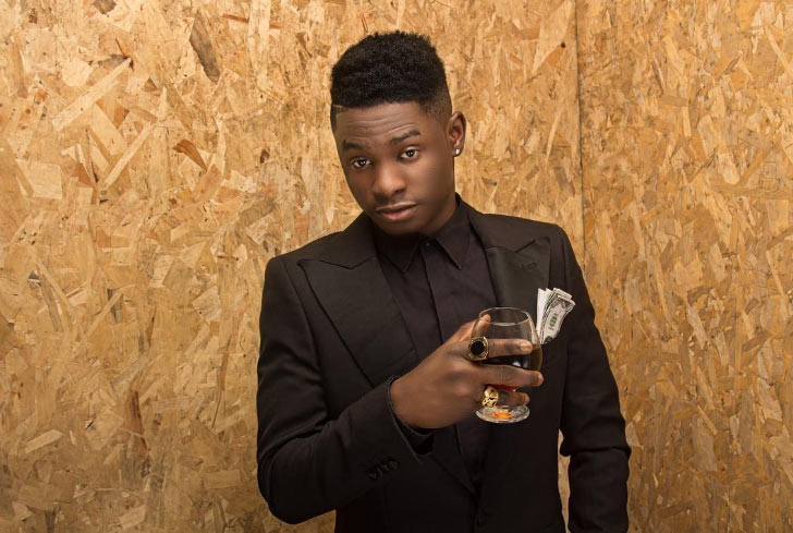 Lil Kesh looks dapper as rapper poses with dollar notes
