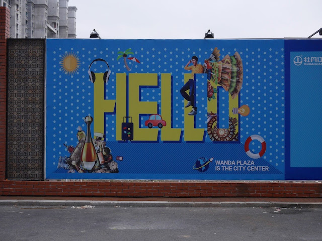 "Wanda Plaza ""Hello"" sign on a wall bordering a construction site in Mudanjiang, China"