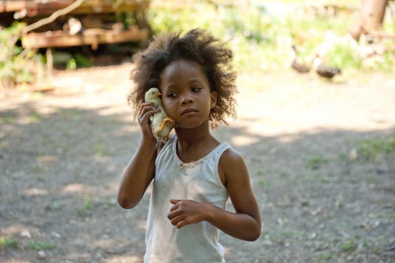 Hushpuppy outside holding a duck up to the side of her head like a telephone