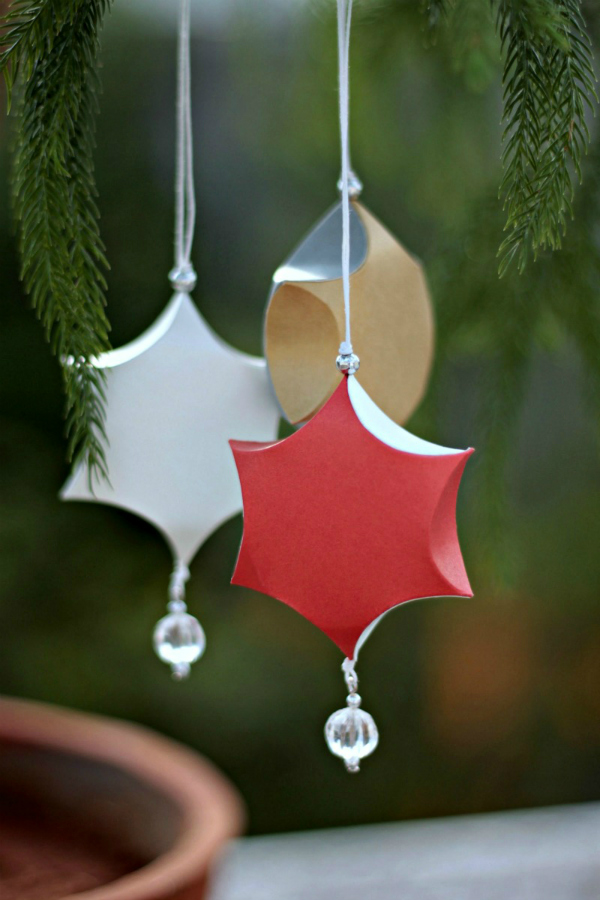 three star-shaped paper ornaments hanging on tree