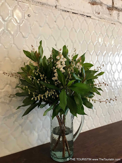 White flowers in a vase on a wooden bench in front of a white subway tiled wall.