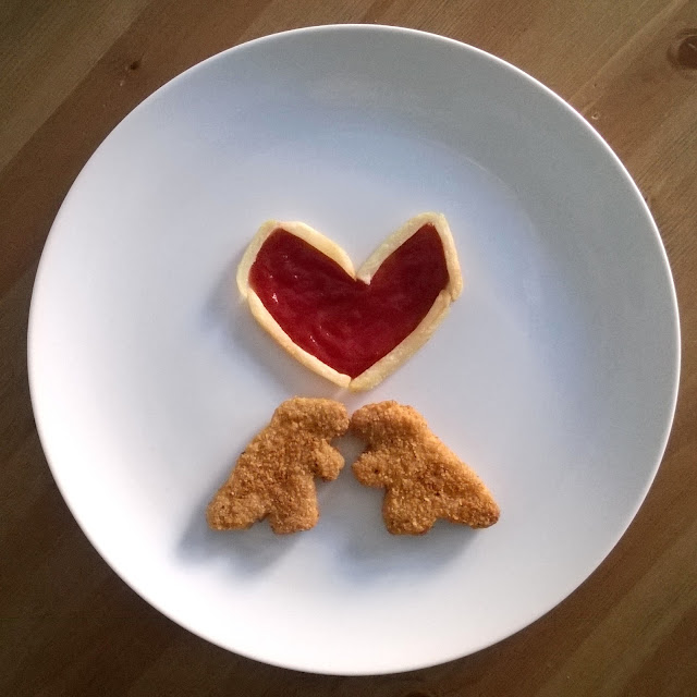 dinosaur food art with ketchup fillded fries heart