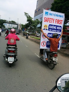 asians on motorbikes carrying huge sign