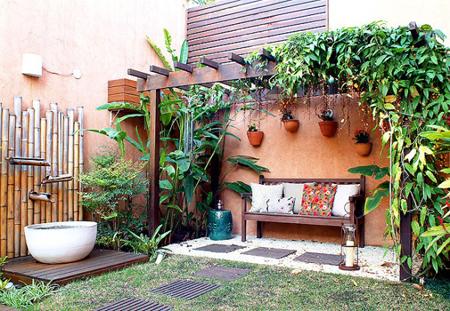 jardim com pergolado e banco rústico com área grama e área com seixos brancos