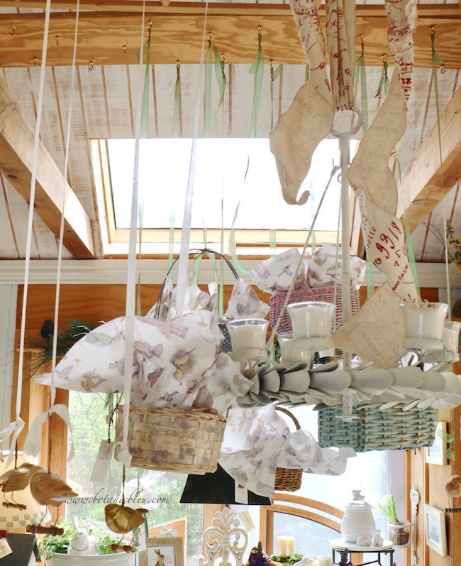 Spring baskets in pastel colors hang from cup hooks in a board between two ceiling beams in the garden shed