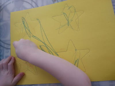 Preschooler coloring her shooting star wand craft