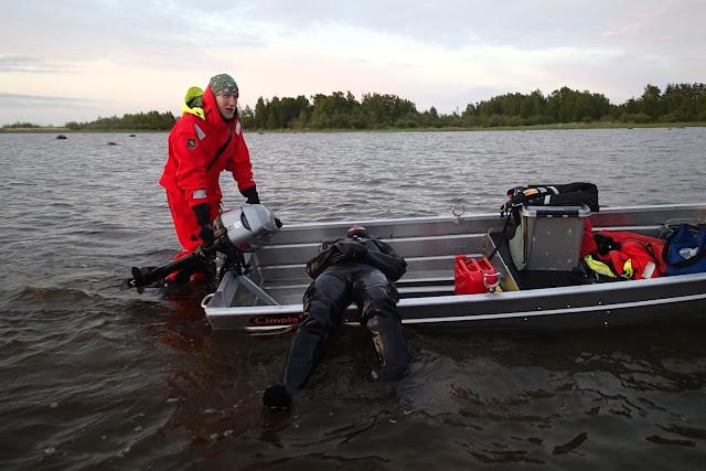 Sukeltaja makaa puoliksi veneessä, toinen ihminen työntää venettä matalassa rantavedessä.