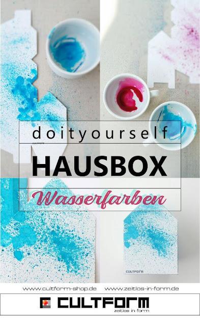 Die Hausbox von Cultform. Ein eindrucksvolles und doch einfaches DIY: kleine Geschenke individuell modern verpacken im aktuellen Watercolor-Trend: Hausbox blaue Farbspritzer, Anleitung