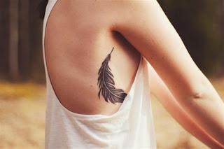 tatuaje pluma en costillas