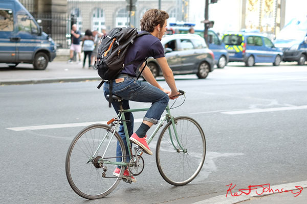 man in blue tee, Levis jean and red converse sneakers rides a light green vintage steel MOTOBECANE road bike. Paris photos by Kent Johnson for Street Fashion Sydney.