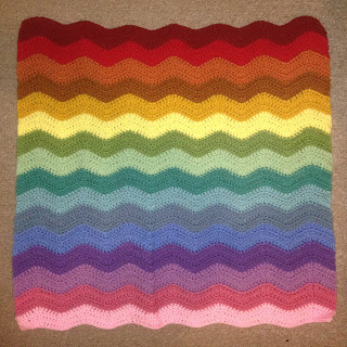 A square blanket with wiggly horizontal lines in colours of the rainbow.