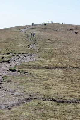An eroded path leading gently uphill with various people walking along it.