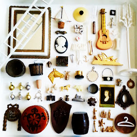 Flatlay of vintage dolls' house miniatures in gold, silver, white, black and brown colours.