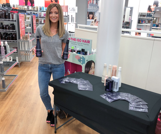 standing next to nexxus keraphix system demo table at ulta