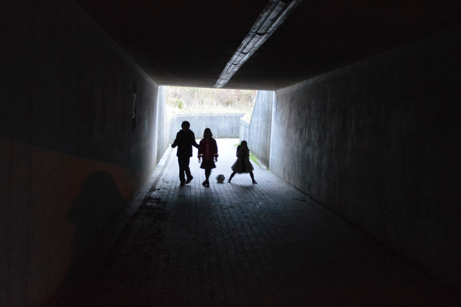 Children tunnel dark light silhouettes