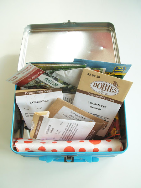 seed tin with lid open showing selection of seed packets