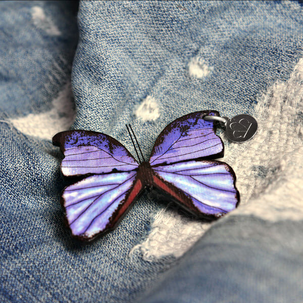 purple and black paper butterfly brooch on distressed denim