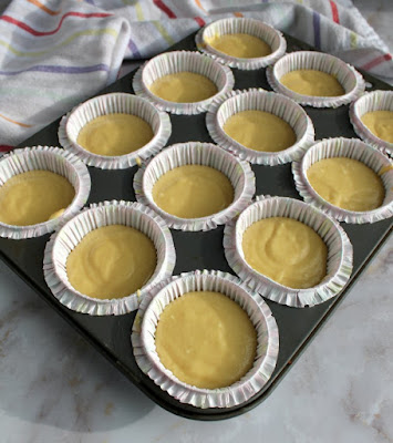 yellow cupcake batter in cupcake liners ready to bake