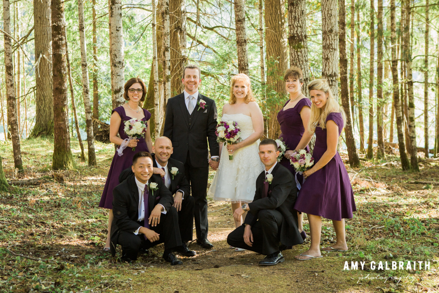 purple and white wedding party standing in the forest