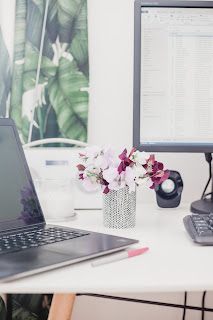 a desk with open laptop and flowers