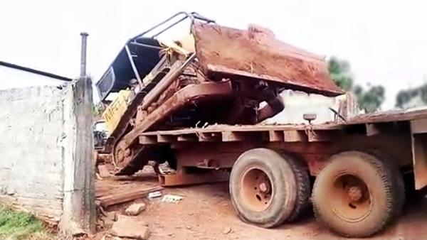Trator de esteiras descendo de cima do caminhão