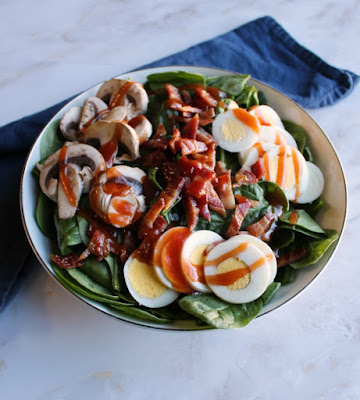 Close up bowl of spinach salad with red dressing drizzled over the top