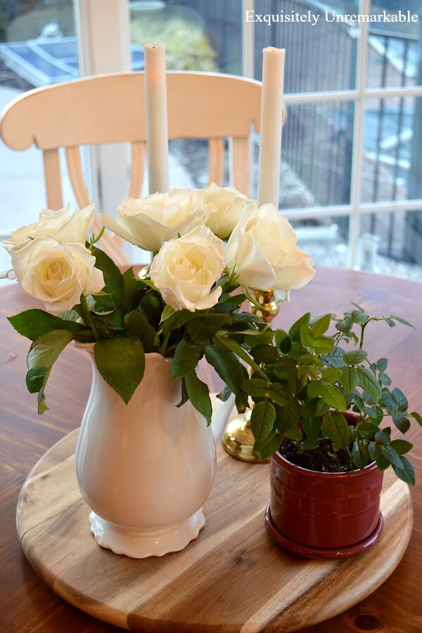 Mini rose bush in new pot on a lazy susan on table next roses in pitcher