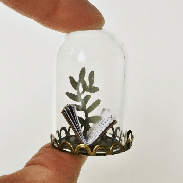 miniature paper scene of a book and green plant in clear glass dome