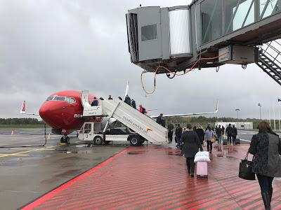 Mennesker på vei mot et Norwegian-fly på en regntung flyplass.