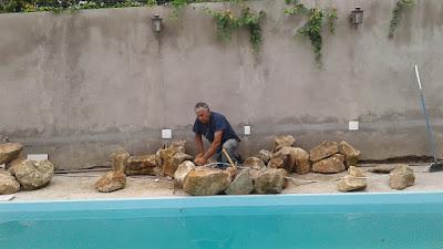 Bizzarri iniciando uma cascata de pedra na piscina com pedras ornamentais tipo pedra moledo na cor bege.