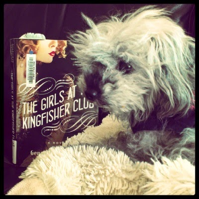 Murchie lays on his sheep pillow with a hardcover copy of The Girls at the Kingfisher Club next to him. Its cover features a white woman in 1920s clothes, her face obscured.